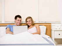 Couple enjoying using laptop in bed Stock Photography