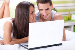 Couple enjoying using laptop in bed Royalty Free Stock Photos