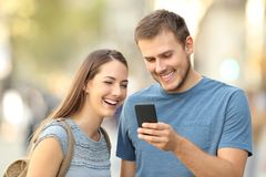 Couple enjoying using a smart phone on the street Stock Photography