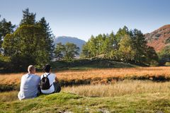 Couple enjoying view. A mixed race couple enjoy a scenic view in Borrowdale, Lake District, Cumbria, UK. Caucasian man, Indian Asian woman royalty free stock images