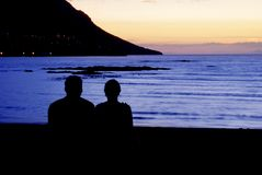 A couple enjoying the view. Of the ocean after sunset in Gordon's Bay, South Africa royalty free stock image