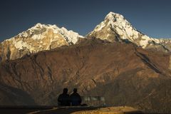 Couple enjoying view of Annapurna South from Poon Hill. Himalaya Mountains, Nepal.  stock photos