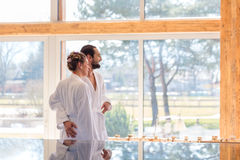 Couple enjoying view on wellness spa pool. Couple on pool looking relaxed throw window of wellness spa wearing bath robe stock images