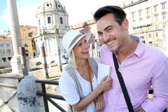 Couple enjoying of visit in Foro Traiano. Coupe in Rome reading guide book by the Foro Traiano Stock Photography