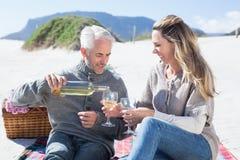 Couple enjoying white wine on picnic at the beach Royalty Free Stock Photo