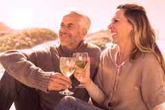 Couple enjoying white wine on picnic at the beach Stock Images