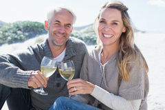 Couple enjoying white wine on picnic at the beach smiling at camera Stock Photography