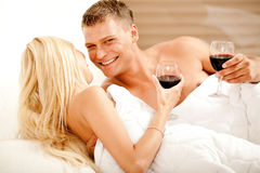 Couple enjoying wine in bed Royalty Free Stock Image