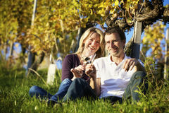 Couple enjoying wine in vineyard. Cheers! Friendly woman and man (couple) sitting in vineyard holding glasses for wine drinking Stock Images