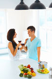 Couple enjoying wine while working in kitchen Royalty Free Stock Photo