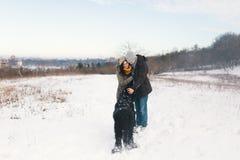 A couple enjoying winter while walking their big black dog havin. Pretty men and women enjoying the snow while walking with their big black curly dog, hugging stock images