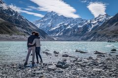 Couple holding on each other at Mount Cook, New Zealand. Couple enjoys beautiful scenery in New Zealand. Romantic couple holding hands. A pair of couple goes on stock photos