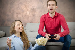 Couple enjoys free time and playing video games. Couple play video game watching home fun watch concept Royalty Free Stock Photography