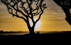A Couple Enjoys the Sunset on San Diego Bay. A couple paused on their walk at the San Diego Bay to enjoy the sunset stock image