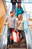 Couple On Escalator In Shopping Mall Together. Smiling At Each Other Stock Image