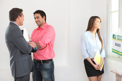 Couple with an estate agent. Couple visitng a property with an estate agent royalty free stock image