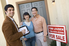 Couple With Estate Agent. Portrait of happy couple with estate agent standing in front of their new house stock images