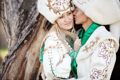 Couple in ethnic costumes embrace on background of textured wood, groom kisses bride at cheek. Royalty Free Stock Photos