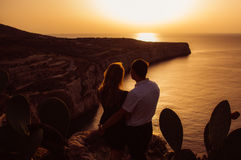 Couple in the evening on the seaside. Looks to the sun stock photo