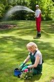 Couple during everyday duties in garden. Married couple during everyday duties in garden Stock Photo