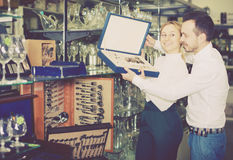 Couple examining cutlery sets in dinnerware store Stock Images