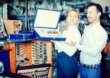 Couple examining cutlery sets in dinnerware store Royalty Free Stock Photos