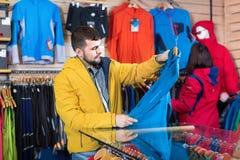 Couple examining track jackets in sports clothes store. Happy cheerful  couple examining track jackets in sports clothes store Royalty Free Stock Photo