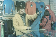 Couple examining track jackets in sports clothes store royalty free stock image