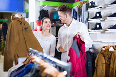 Couple examining various coats in sports store Stock Images
