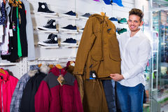 Couple examining various coats in sports store Royalty Free Stock Image