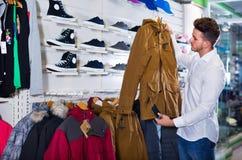 Couple examining various coats in sports store stock photos