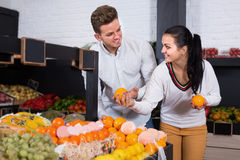 Couple examining various fruits in grocery store Royalty Free Stock Photo