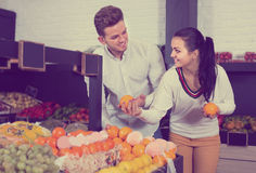 Couple examining various fruits in grocery store stock photography