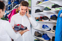 Couple examining various sneakers in sports store Stock Photo