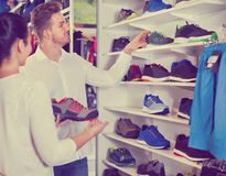 Couple examining various sneakers in sports store Royalty Free Stock Photos