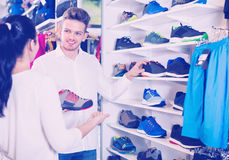 Couple examining various sneakers in sports store Royalty Free Stock Images