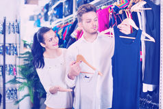 Couple examining various sports clothes in sports store Stock Image