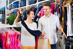 Couple examining various sports clothes in sports store Royalty Free Stock Images