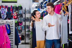 Couple examining various sports clothes in sports store Stock Photos