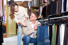 Couple examining various trousers Stock Images