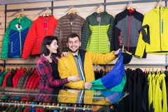 Couple examining windcheaters in store Stock Photo