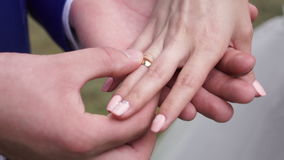 The couple exchange wedding rings. Wedding rings and hands of bride and groom. young wedding couple at ceremony. matrimony. man and woman in love. two happy stock video footage