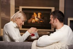 Couple exchanging gift at home Stock Images