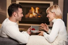 Couple exchanging gift at home Stock Photos