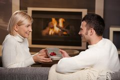 Couple exchanging gift at home. Young romentic couple sitting on couch in front of fireplace at home, men giving gift, side view stock photography
