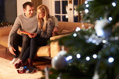Couple Exchanging Gifts By Christmas Tree stock photography