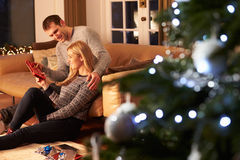Couple Exchanging Gifts By Christmas Tree royalty free stock photos