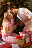 Couple Exchanging Presents In Front Of Tree Stock Photo