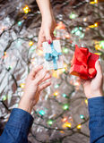 Couple exchanging Valentines presents. With festive background Royalty Free Stock Image