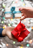 Couple exchanging Valentines presents. With festive background Royalty Free Stock Images
